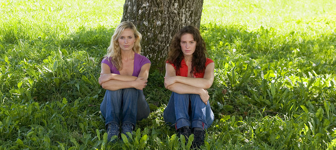 unhappy lesbian couple sitting under tree
